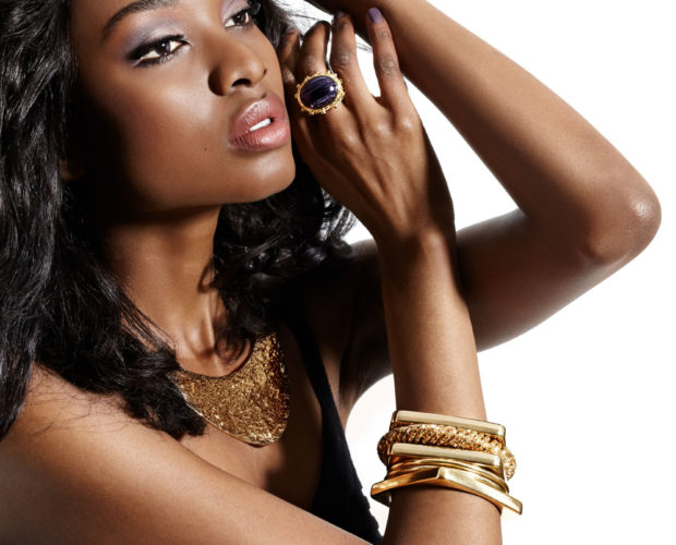 37773885 - african model with large hairstyle posing in golden jewelry.