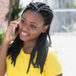 50825658 - laughing african american woman in a yellow shirt at mobile phone
